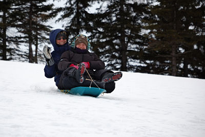 Family member sledding down a hill with a child